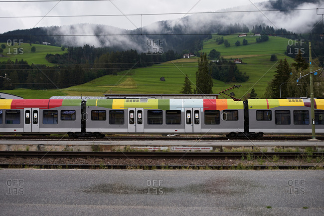 Contemporary train with colorful roof moving on rails near green hills on cloudy day in nature