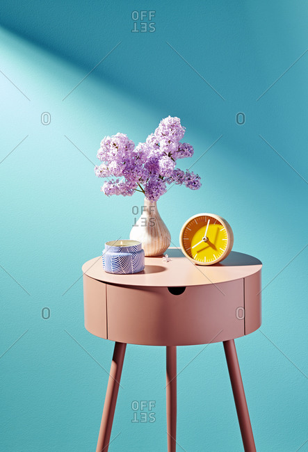 Pink Nightstand with Candle, Clock and Flowers on Blue