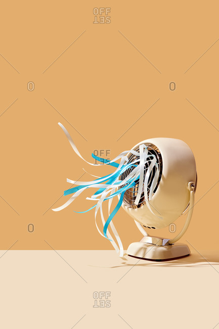 Tabletop Fan Blowing Blue Ribbons on Colored Background
