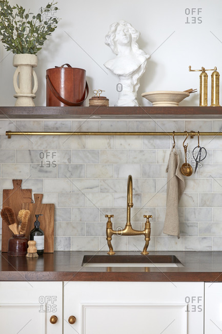Modern kitchen with fancy brass finishes including faucet