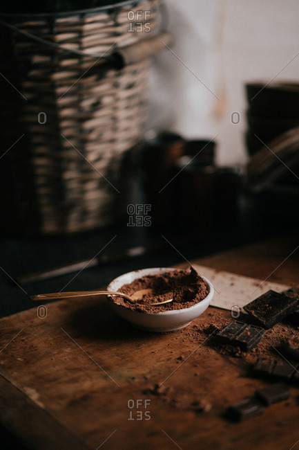 Baking chocolates on cutting board in moody lighting with a mess of cocoa powder