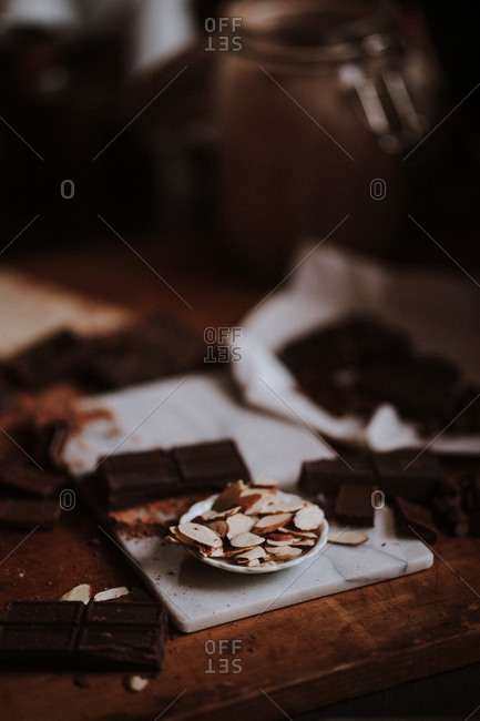 Baking chocolates and almond pieces on cutting board in moody lighting