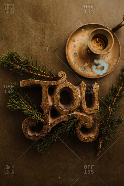 Golden joy sign with pine branches by a candlestick holder