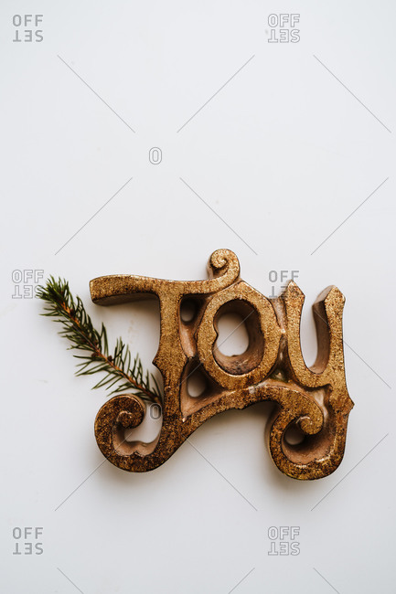 Joy sign on white background with pine branches