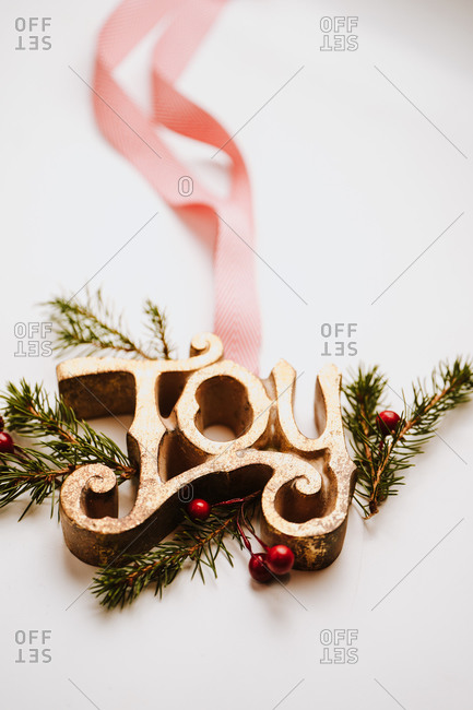 Close up of joy sign with ribbon on white background with pine branches and holly berries