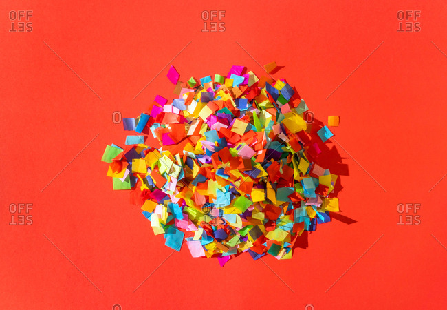 A pile of colorful confetti pieces on red background