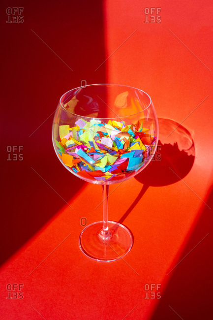 A wine glass filled with colorful confetti pieces on red background