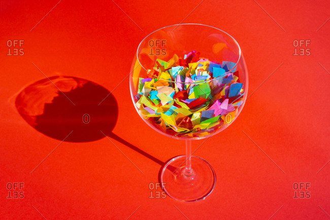 A large wine glass filled with colorful confetti pieces on red background