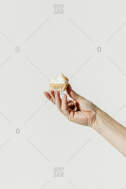 Woman's hand holding a small slice of lemon tart with meringue