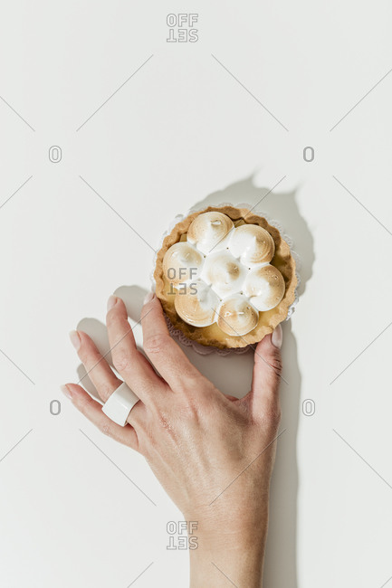 Woman's hand touching a miniature lemon tart with meringue