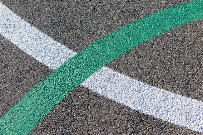 Green and white curved lines painted on concrete