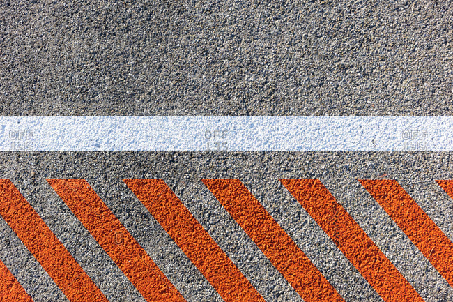 Red diagonal lines and one white straight light painted on concrete