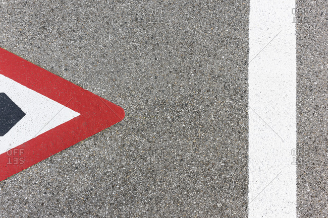 Red and white triangular traffic symbol painted on concrete