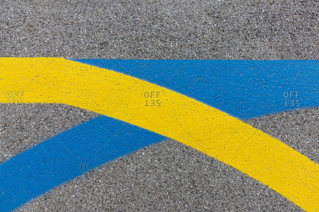 Yellow and blue curved lines painted on concrete