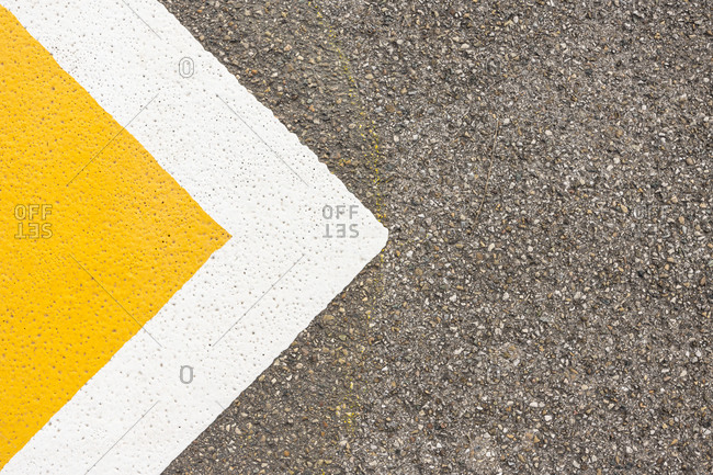 Yellow triangular traffic symbol painted on concrete