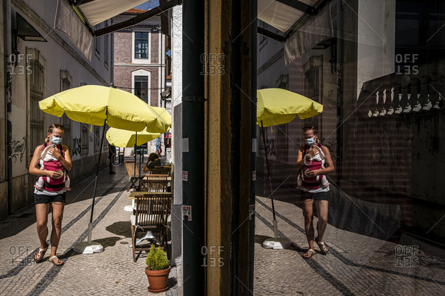 Aveiro, Portugal - August 24, 2020: Mother carrying her baby in downtown Aveiro