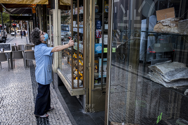 Porto, Portugal - August 27, 2020: Employee checking the window of her grocery store