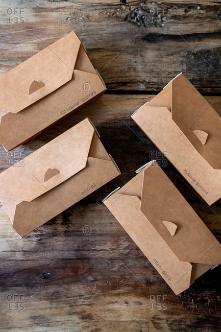 Overhead view of cardboard takeout boxes on rustic wooden surface