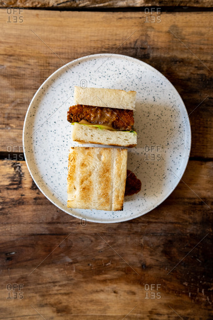 Top view of a katsu sando sandwich on plate on wooden table