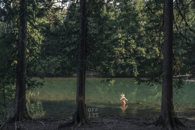 Man walking into a green lake in the summertime while wearing a sun hat