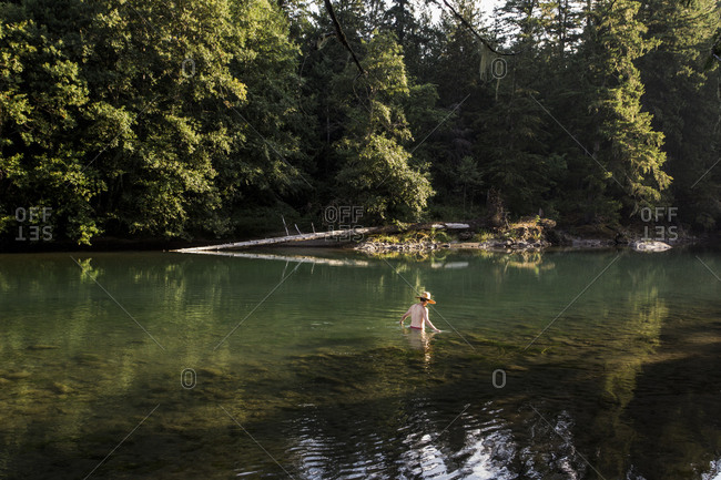 Man wearing a sun hat walking in a green lake in the summertime