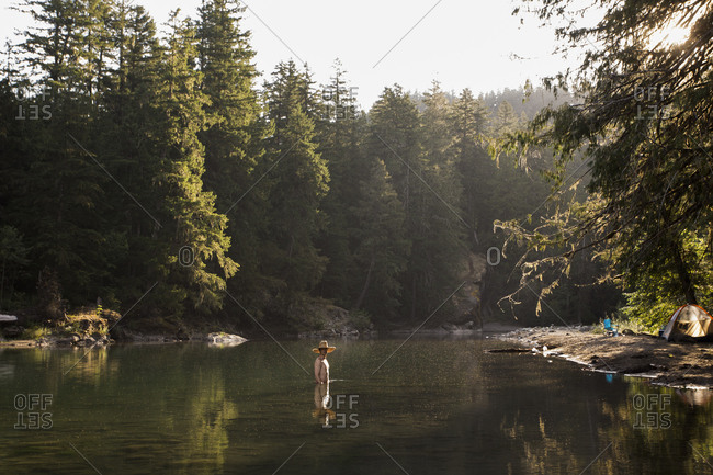 Man swimming in a green lake in the summertime near campsite
