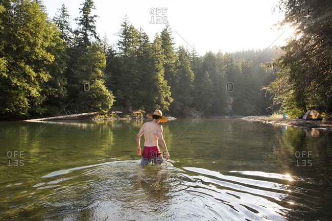 Rear view of man walking into a green lake in the summertime while wearing a sun hat