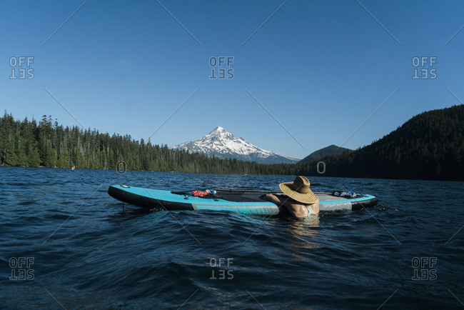 A young woman enjoys a summer day while resting on the edge of a standup paddleboard on Lost Lake in Oregon