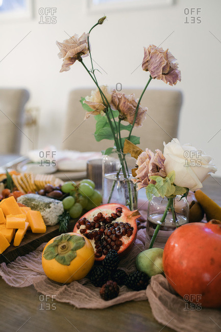 Fresh fruit and cheese board on a table with drying flowers