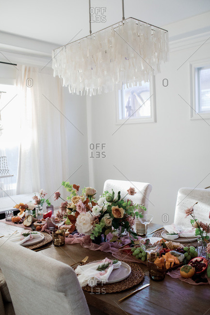 Flowers and snacks arranged on a set table under a modern chandelier