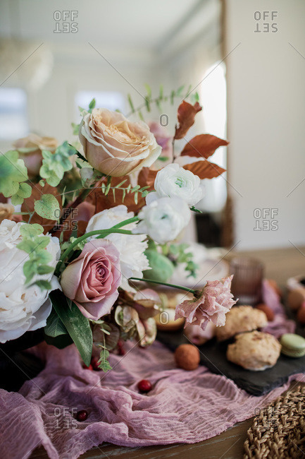 Beautiful floral arrangement on a party table with food in the background