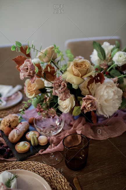 Beautiful floral arrangement on a party table with glasses and pastries