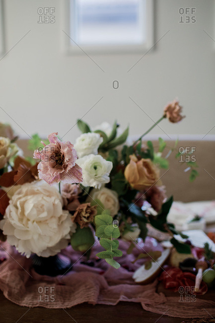 Floral arrangement on a party table with food