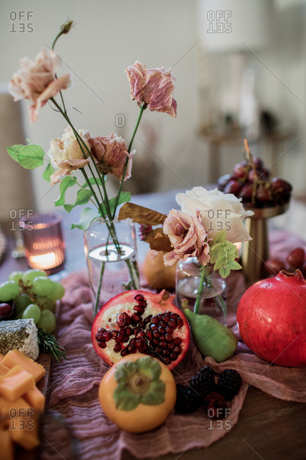 Fruit and cheese board on a table with drying flowers
