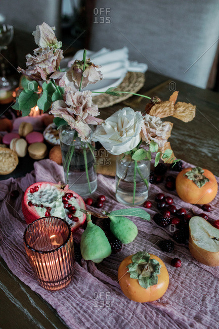Candles on table with fresh fruit and drying flowers