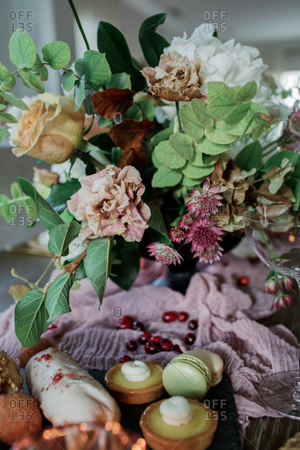 Flowers on a table with sweet pastries and berries