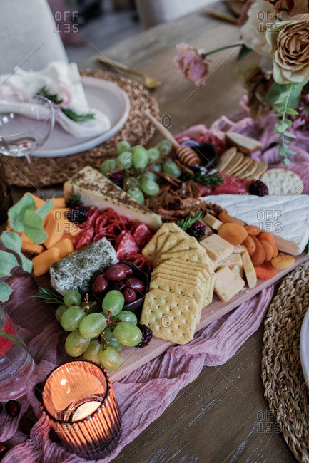Fruit and cheese board on a dinner table set for party with candles