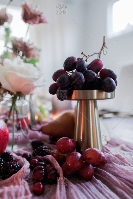 Grapes on a table with flowers in the background