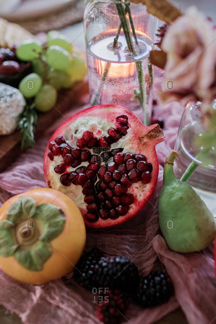 Close up of pomegranate and other fruit on a pink cloth