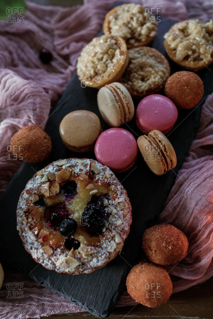 Delicious pastries served on slate board and pink cloth