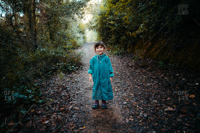 Four years old little girl walking in the forest wearing a huge jacket
