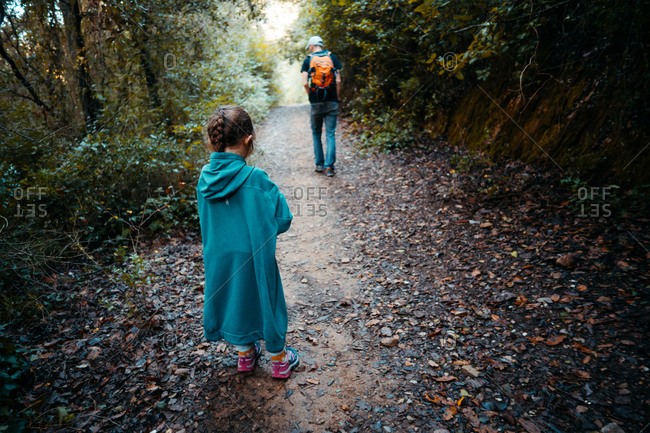Four years old little girl walking in the forest with a huge jacket from her father
