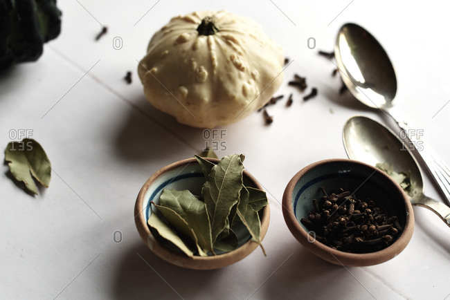 Pumpkin, bay leaves and cloves in autumn on white surface