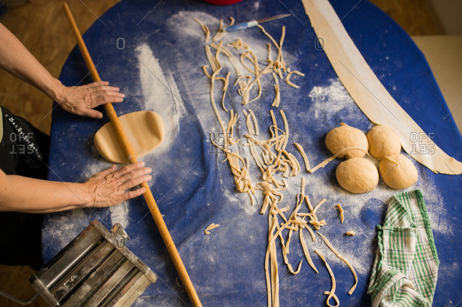 Woman rolling out dough for homemade pasta on blue table