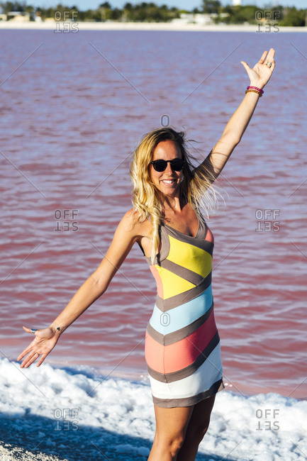 Happy woman traveler with open arms wearing colorful dress by pink waters at Las Coloradas salty lakes in Yucatan