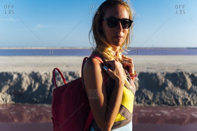 Serious woman traveler near pink lake carrying backpack in Las Coloradas, Yucatan