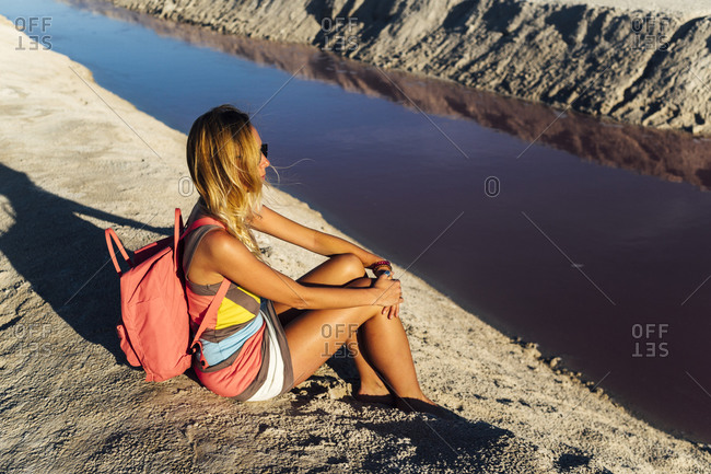 Side view of stylish middle aged tourist seated on salty lake with backpack enjoying sunset near pink lake in Las Coloradas, Mexico
