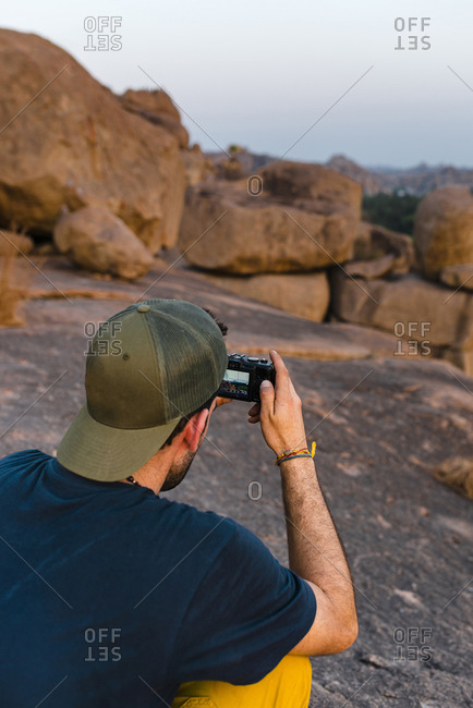 Rear view of resolute hiker with baseball cap taking pictures with digital camera at dusk on rocky mountain in Hampi Island, India, Karnataka