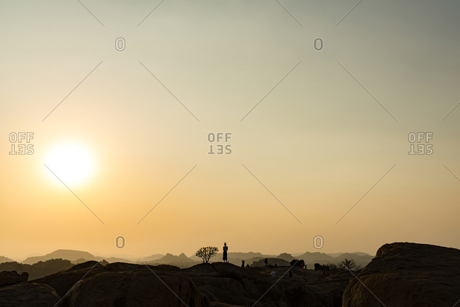 Unrecognizable silhouette of tourists at sunset view at Monkey Temple in Hampi