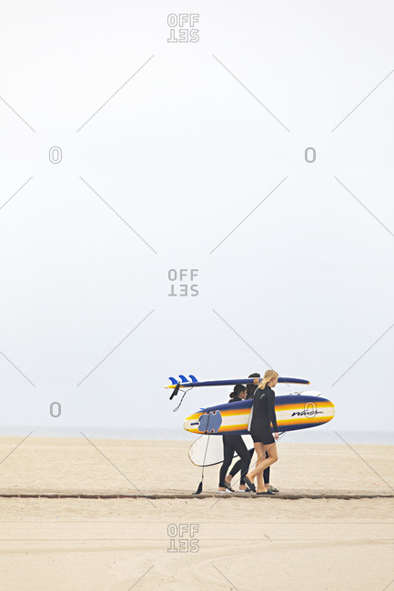 Santa Monica, California - July 22, 2020: Three young women walking on beach and carrying surfboards by the Pacific Ocean